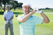 Golfer swinging his club with friend behind him on a sunny day at the golf course