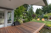 stock photo of ponds  - A perspective view of a contemporary Pacific Northwest home with a deck bridging a pond that leads to a pair of modern yellow loungers in a landscaped yard - JPG