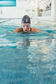Fit swimmer coming up for air in the swimming pool at the leisure center