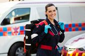 beautiful young female paramedic carrying lifepack in front of ambulance