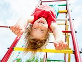 stock photo of upside  - Little girl having fun playing on monkey bars - JPG