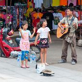 Kanchanaburi, Thailand - May 23, 2014: Unidentified Children Sing And Adult Play Guitar On The Stree
