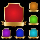 Set of varicolored decorative golden shields with banner isolated on black background.
