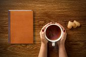 woman with cup of tea, cookies and book on wooden table