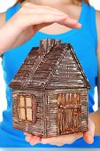 Small wooden house in hands, close up