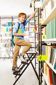Boy climbing on step ladder in library