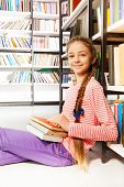 Smiling girl with books sit on floor in library