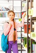 Girl with braid stands near bookshelf