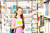 Smiling girl standing among library shelves