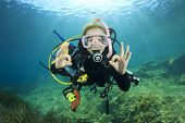 Happy young woman scuba diver signals okay