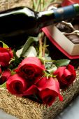 stock photo of gift basket  - Roses Wine and Chocolates in a large wicker tray - JPG