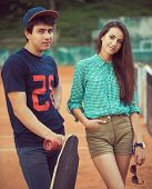 Young Couple Standing On A Skateboard On The Tennis Court