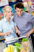 Couple discussing the shopping list and chosen products standing near the shopping trolley full of f