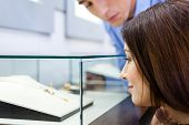 foto of jewel-case  - Girl with man selects expensive jewelry at jeweler - JPG