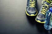 Sport shoes and water on grey background