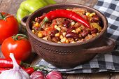 stock photo of saucepan  - hot chili con carne in a saucepan and ingredients on the table - JPG