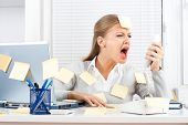 Young businesswoman shouting on telephone at her office.