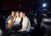 Smiling family of three watching film in cinema theater