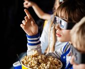 Girl pointing while watching 3D movie with siblings at cinema theater