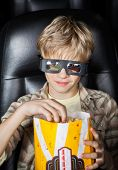 Portrait of boy eating popcorn while watching 3D movie in cinema theater