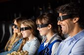 Smiling family of four watching 3D movie in cinema theater