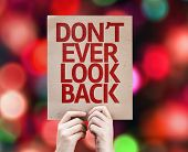 Don't Ever Look Back written on colorful background with defocused lights