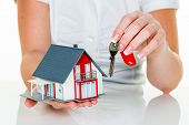 an agent for property with a house and a key. successful leasing and home sales by real estate agents.