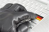 Hacking Germany Concept With Hand Wearing Black Leather Glove Pressing Enter Key With Flag Overlaid