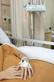 Patient on hospital bed, focusing on her hand