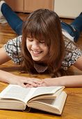 Happy teenage girl reading a book on the wooden floor
