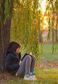 Pretty teenage girl reads the book