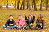 Teenage boys and girls having fun in the nature on beautiful autumn day
