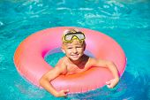 Happy Young Boy Floating in Swimming Pool on Raft