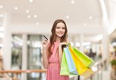 sale, consumerism, money and people concept - happy young woman with shopping bags and credit card in mall