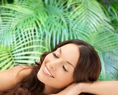 beauty, people and health concept - beautiful young woman lying with closed eyes over green palm leaves background