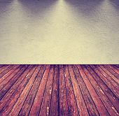 an image of an empty room with gray tones and a brown wood floor toned with a retro vintage instagram filter