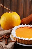 Composition of homemade pumpkin pie on plate and fresh pumpkins on wooden background