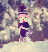 a cute tiny miniature snowman with a scarf and hat on toned with a retro vintage instagram filter