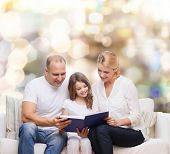 family, childhood, holidays and people - smiling mother, father and little girl reading book over lights background