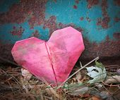 picture of discard  -  a discarded paper heart on a rusty background with leaves toned with a retro vintage instagram filter effect  - JPG