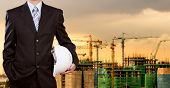 Businessman Holding Safety Helmet With Construction Site In Background
