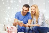 love, family, finance, money and happiness concept - smiling couple counting money with piggybank on table at home