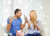 love, family, finance, money and happiness concept - happy couple with cash money and piggybank cheering at home