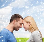 love, happiness, people and family concept - smiling couple looking at each other over blue sky, snow and grass background
