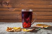 mulled wine in a glass with spices, ginger, lemon, cinnamon and fruit on a white background