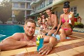 Cheerful young people sitting by swimming pool, drinking, having fun, enjoying holiday.