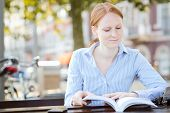Businesswoman Reading A Book In A City