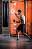 stock photo of pugilistic  - Young man boxing workout in an old building - JPG