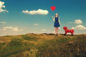 image of horse girl  - Young girl with a red ball in hand and with a toy horse walks outdoors - JPG