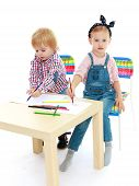 Girl and boy sitting at the table draw.
